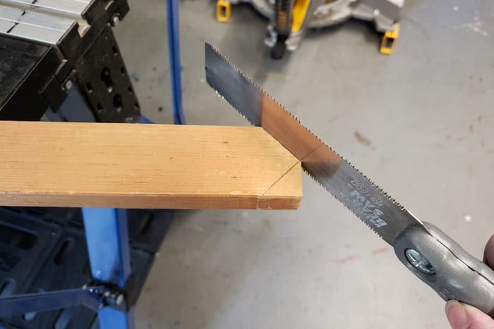 Cutting a point on a 1x2 board with a pull saw.