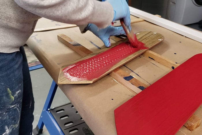 Painting fan blades with red exterior paint.