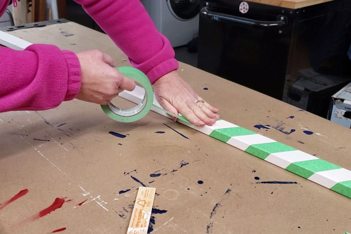 Wrapping a white 1x2 pole with green painter's tape