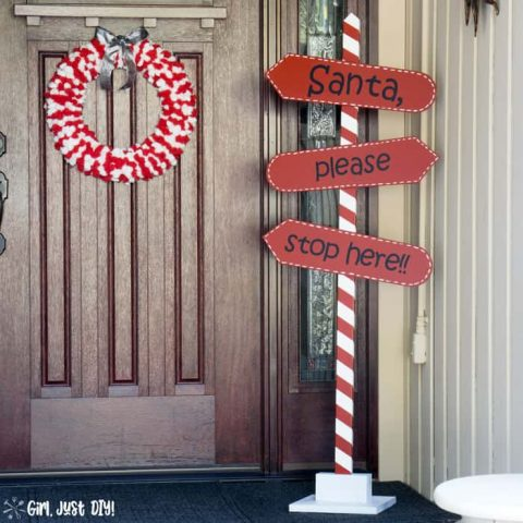 Red and white christmas wreath on porch with santa stop here sign.