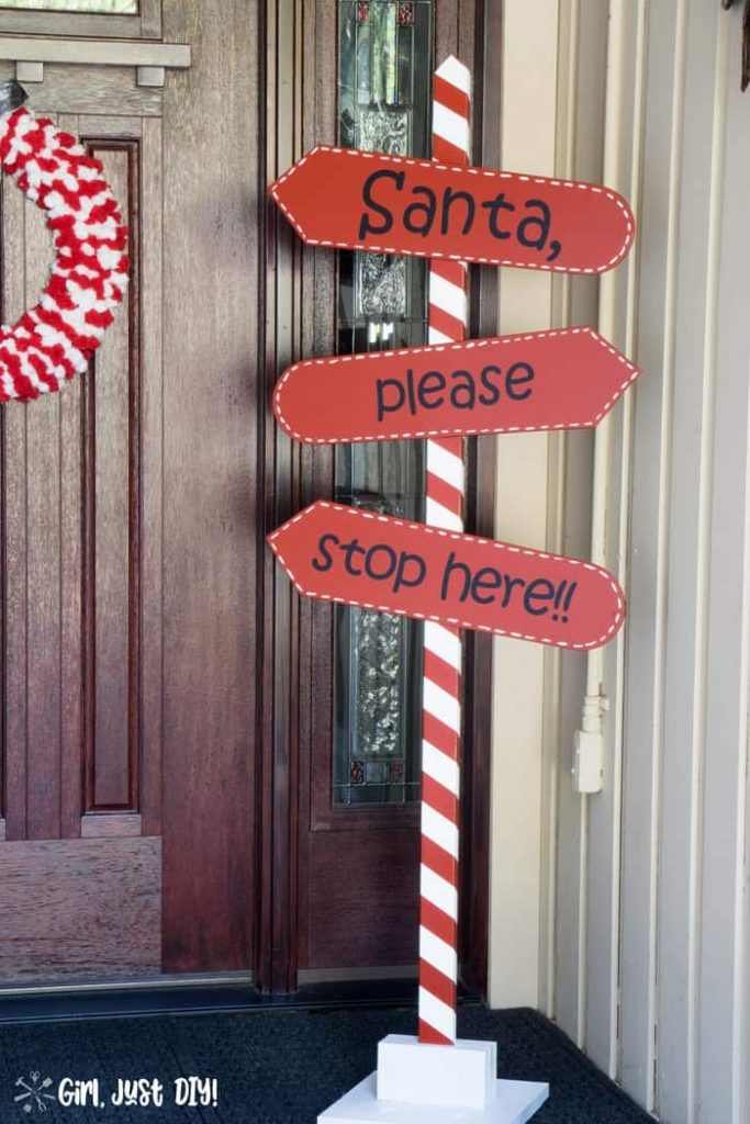 Red and White DIY Santa Stop Here sign on porch by front door with Christmas wreath.