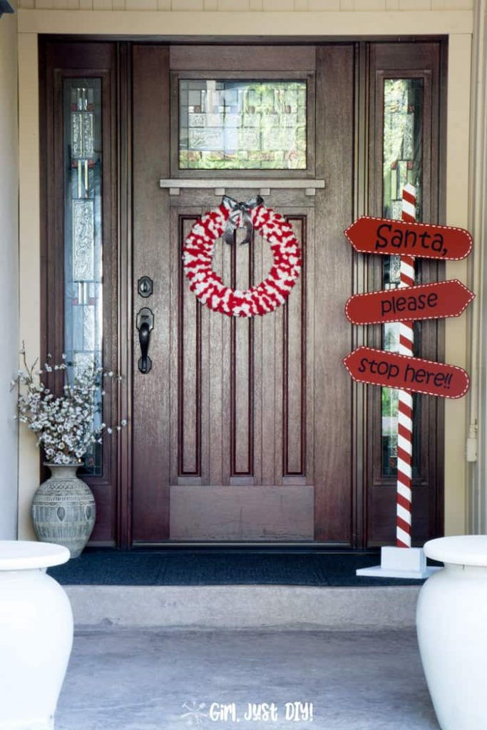 Tall image of DIY Santa Stop Here Sign on front porch next to door.