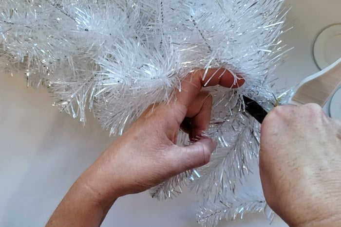 Using wire cutters to cut a branch from a silver metallic Christmas Tree.