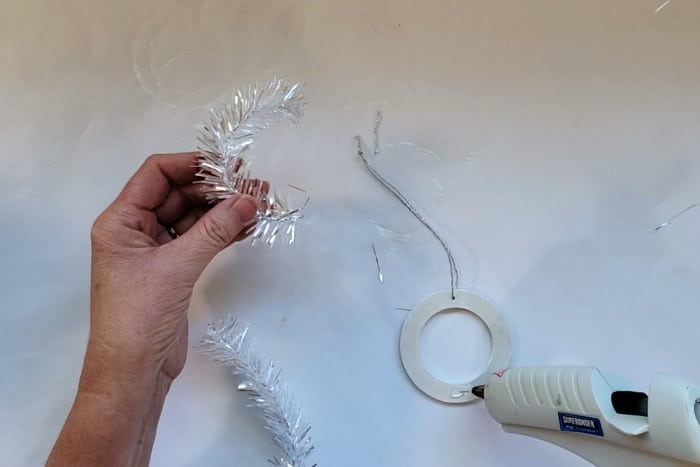 Curved tinsel branch getting hot glued to painted wood circle.