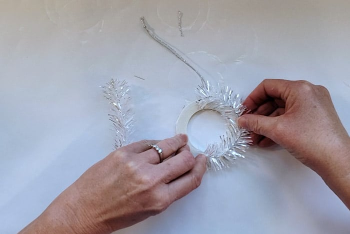 Holding tinsel in place while hot glue dries.
