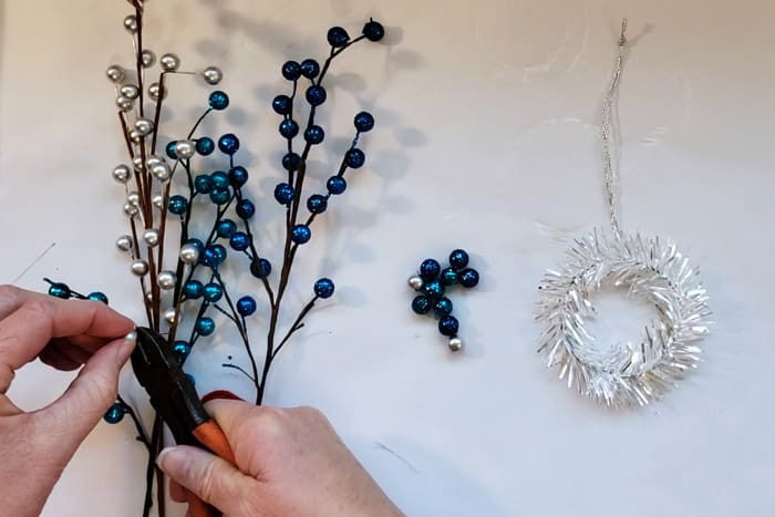 Using wire cutters to cut glittery berries from christmas picks.