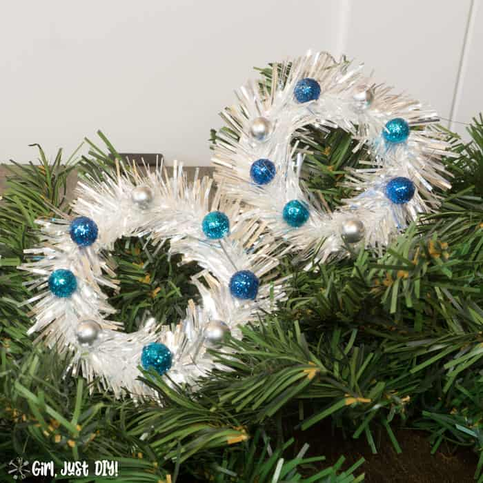 Side by side tinsel mini wreath ornaments on green tree.
