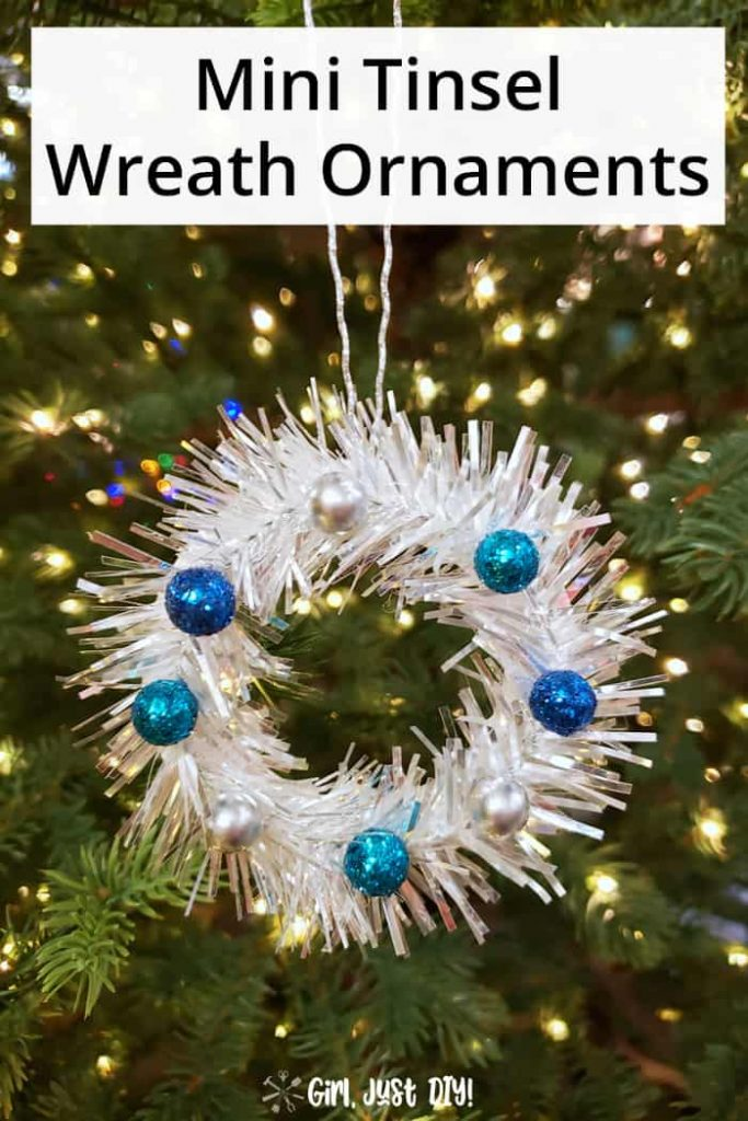 Tinsel Mini Wreath Ornament with blue berries hung on lighted tree.
