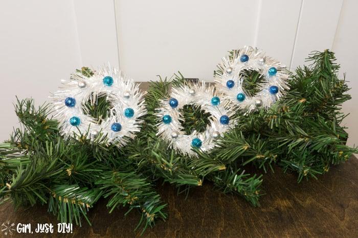 Three tinsel mini wreath ornaments on faux tree spray