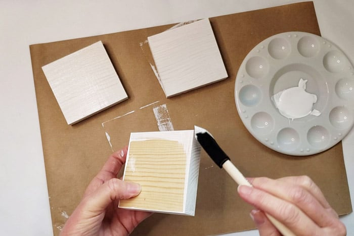 Wood blocks being painted with white paint.