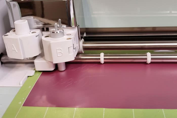 Cricut machine cutting through rose gold vinyl.