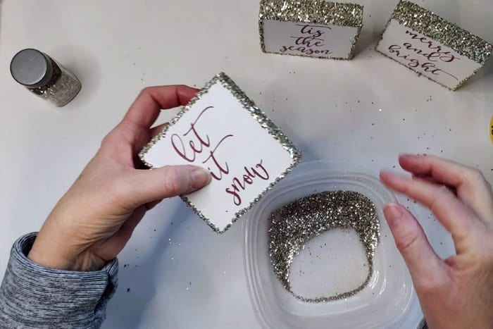 Dipping Christmas Wood Signs into chunky glitter.