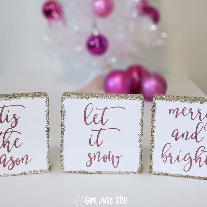 Let it Snow Christmas sign flanked by two others in front of white christmas tree with pink ornaments