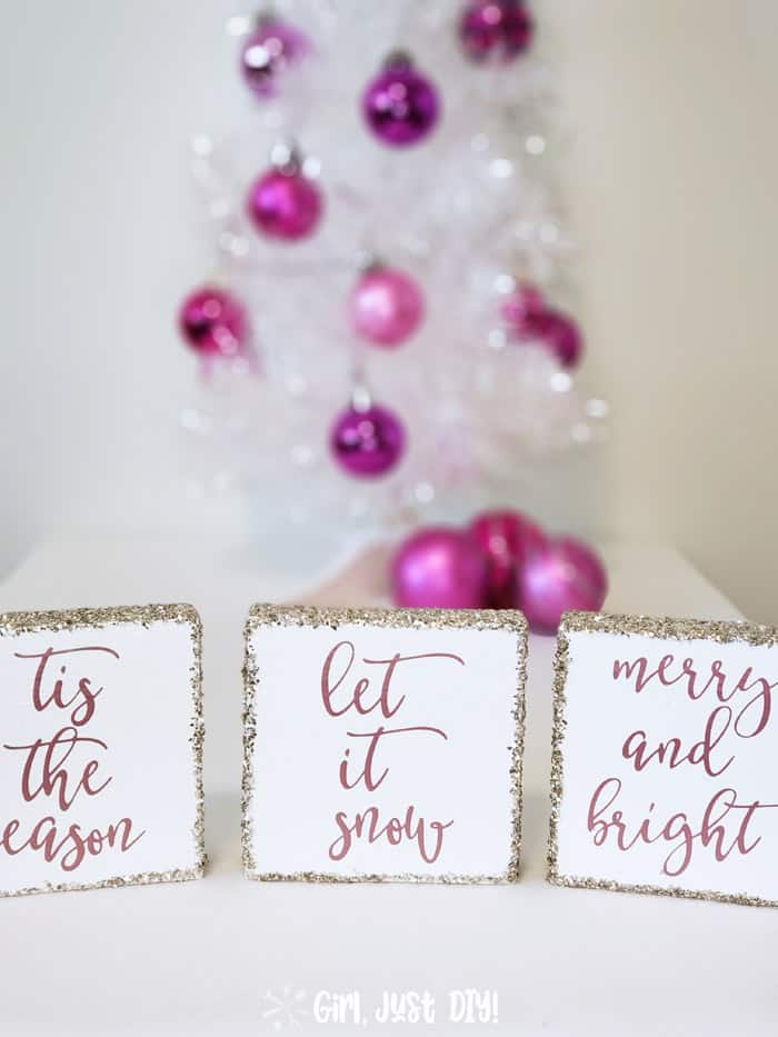Wood christmas signs in front of a white tree with colorful bulbs