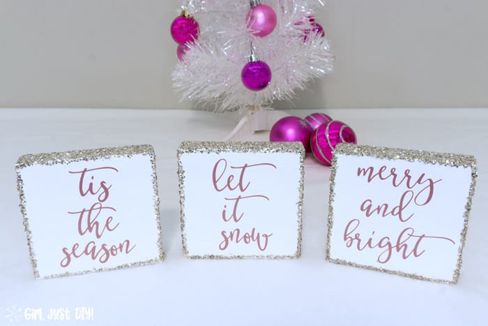 Three Christmas wood signs in front of White Christmas tree with pink ornaments