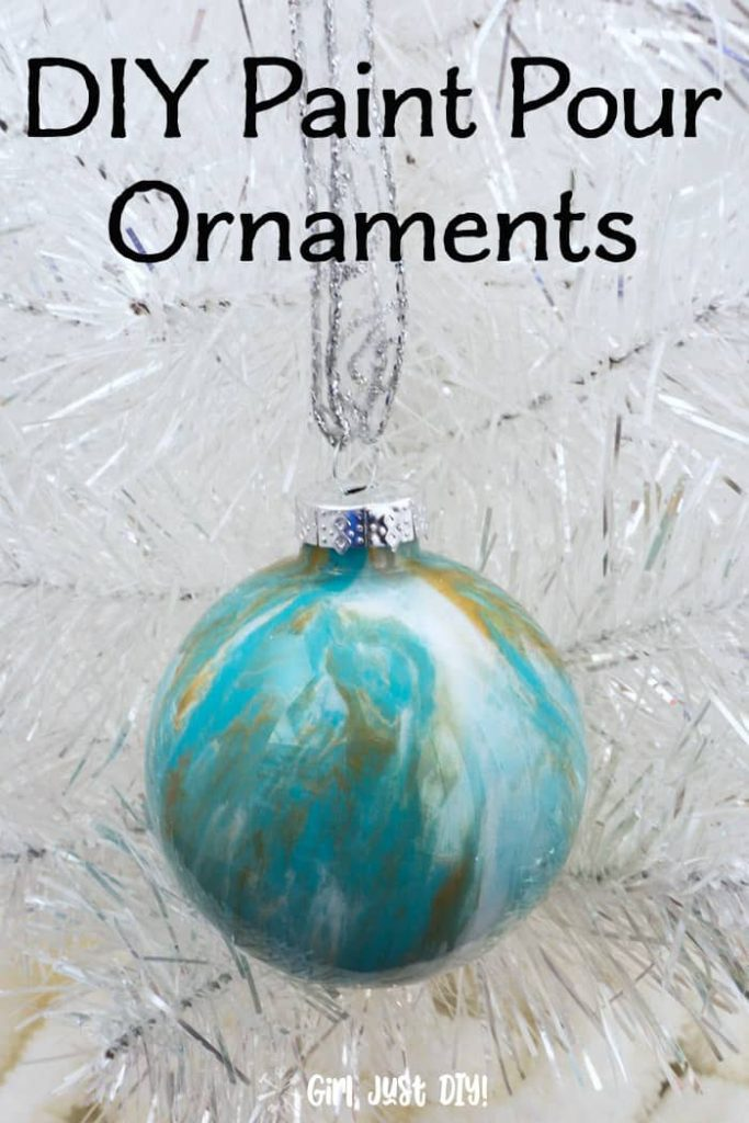 Turquoise pain pour ornament hanging on white christmas tree by silver ribbon.