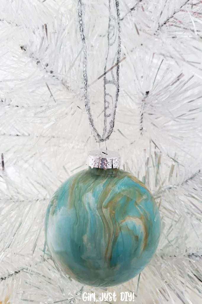 Turquoise and gold ornament hanging against white Christmas tree.