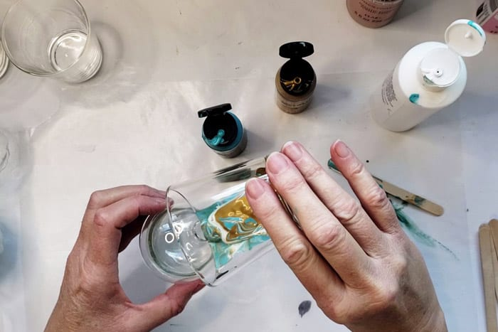 Pouring paint pour mixture into glass ornament bulb.