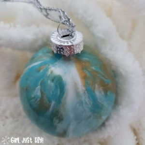 Turquoise, gold and white paint pour Chirstmas ornament on fluffy white yarn.