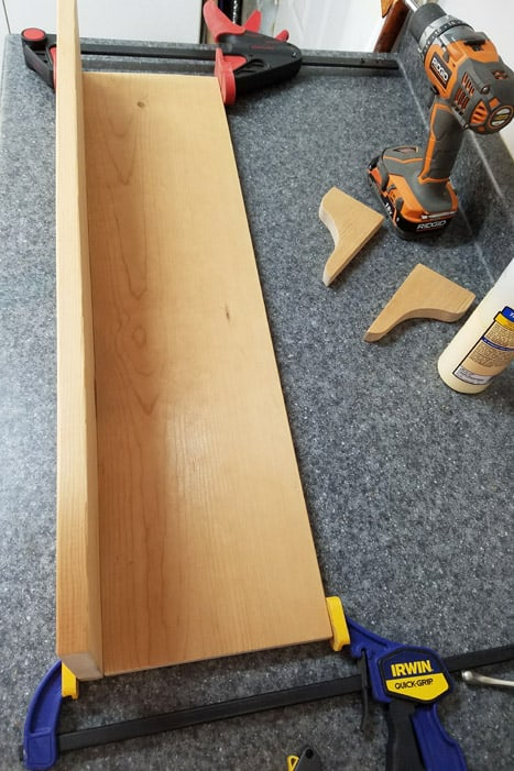 Boards glued and clamped together at right angles to create coat rack.