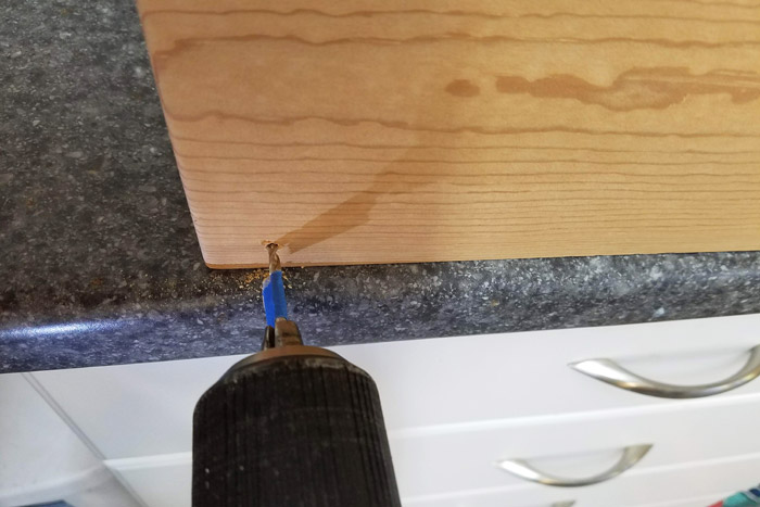 Drilling pilot holes into wood shelf