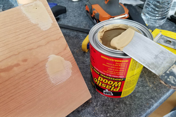 Filling screw holes with putty knife filled with plastic wood filler