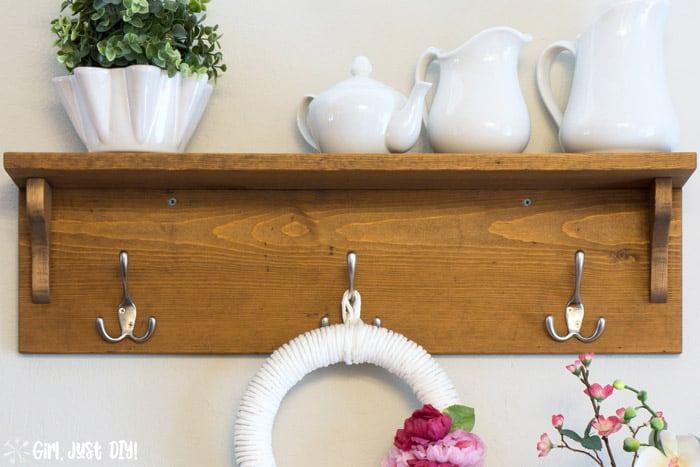 Front image of DIY Wooden coat rack attached to wall with wreath hanging from center hook and white vases on the shelf.