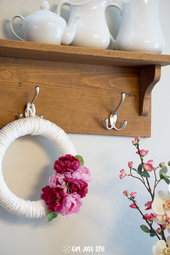 close-up of diy coat rack with a wreath hung in the center.
