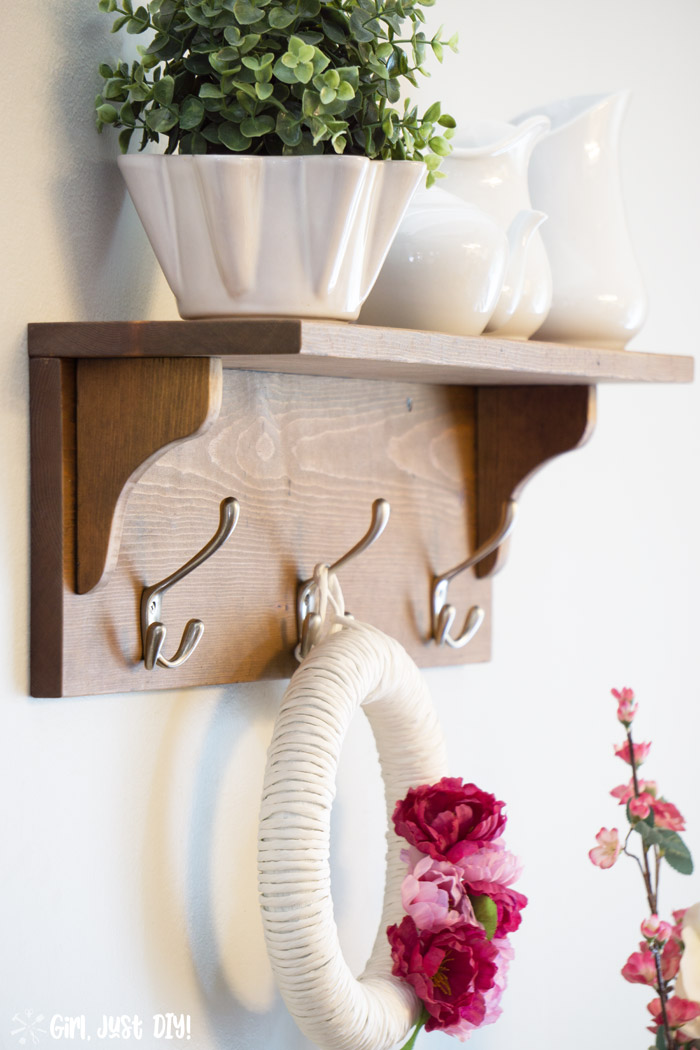 Wooden coat rack attached to wall with wreath hanging from center hook and white vases on the shelf.