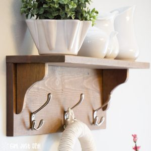 Closeup shot of DIY Wooden coat rack attached to wall with white vases on the shelf.