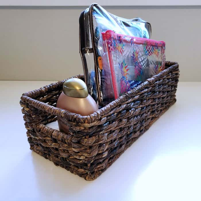 Dark wicker cd basket on white table holding plastic toiletry bags.