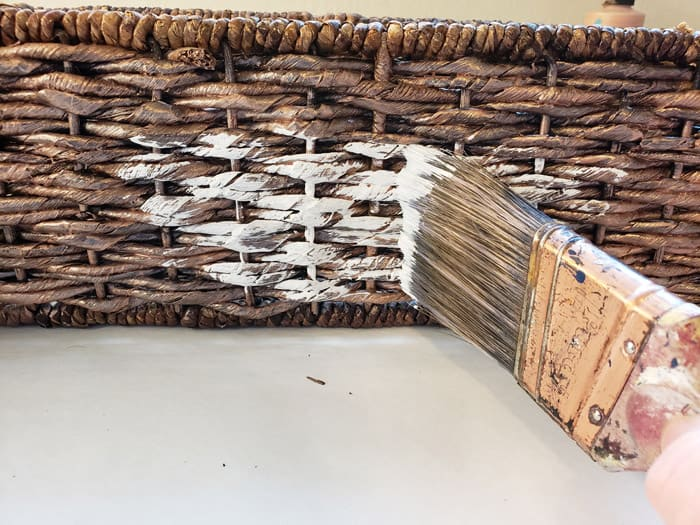 Paint brush whitewashing dark wicker basket.