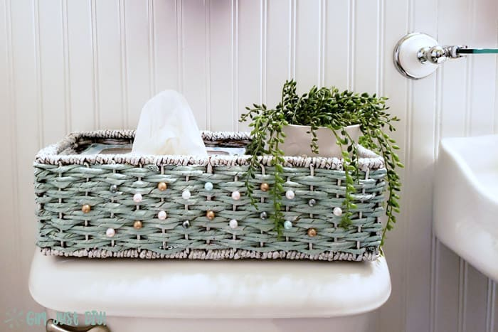 Painted wicker basket on back of toilet tank