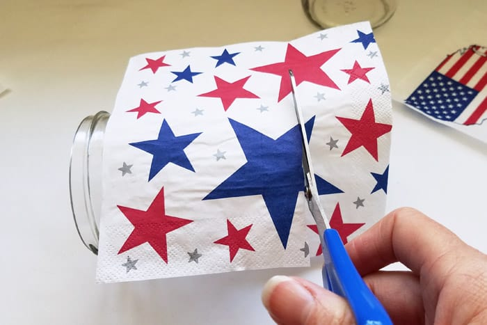 Cutting 4th of july napkin to size on jar