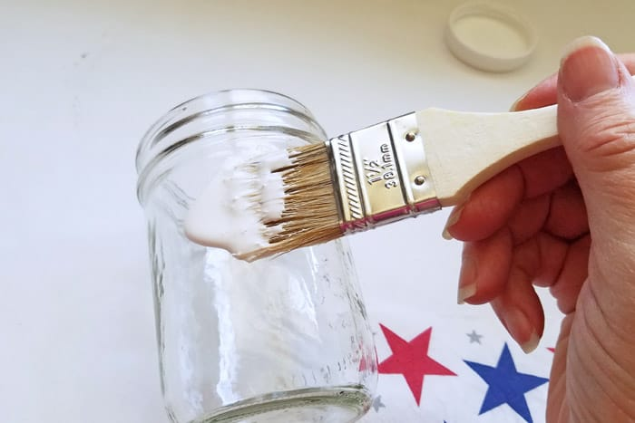 painting mod podge onto mason jar