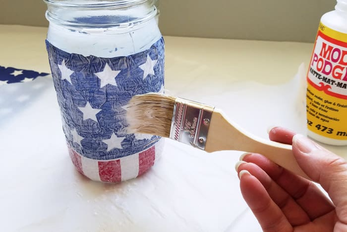top coating patriotic napkins on mason jar with mod podge