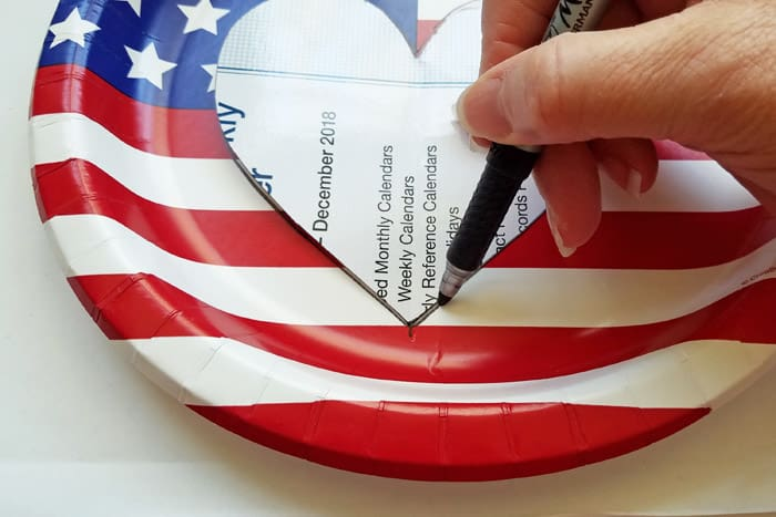 Tracing a heart onto a american flag paper plate