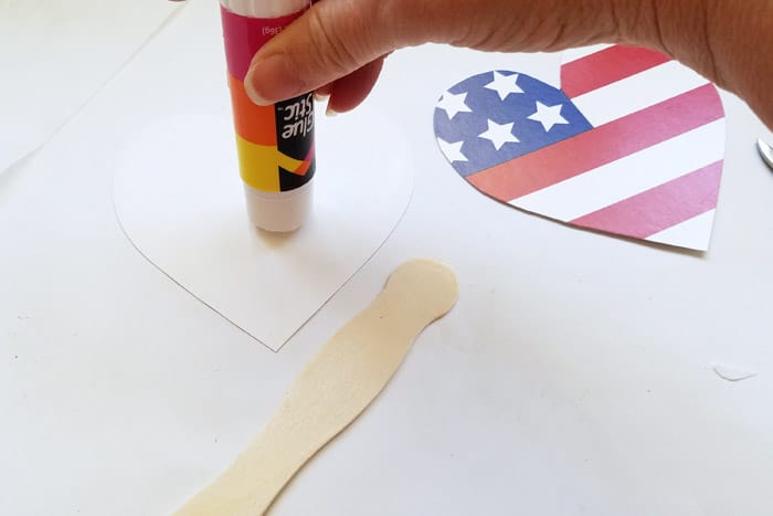 Putting glue stick onto the back of a cut out heart shape.