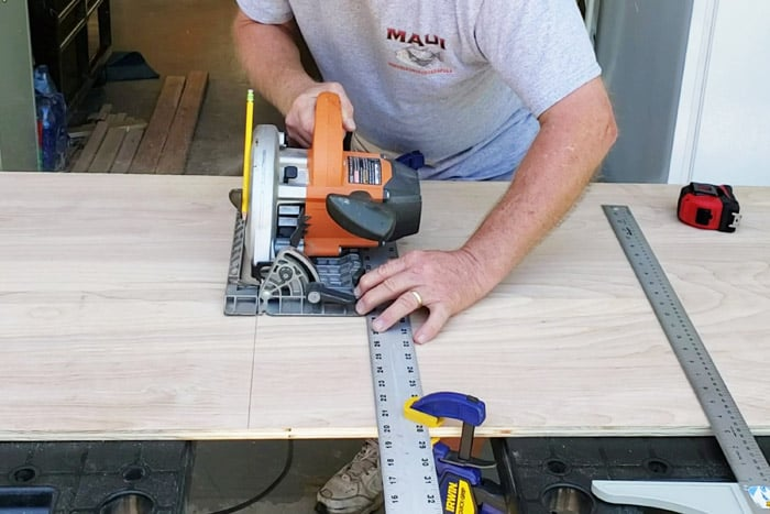 Cutting plywood with circular saw and straight edge clamped to board.