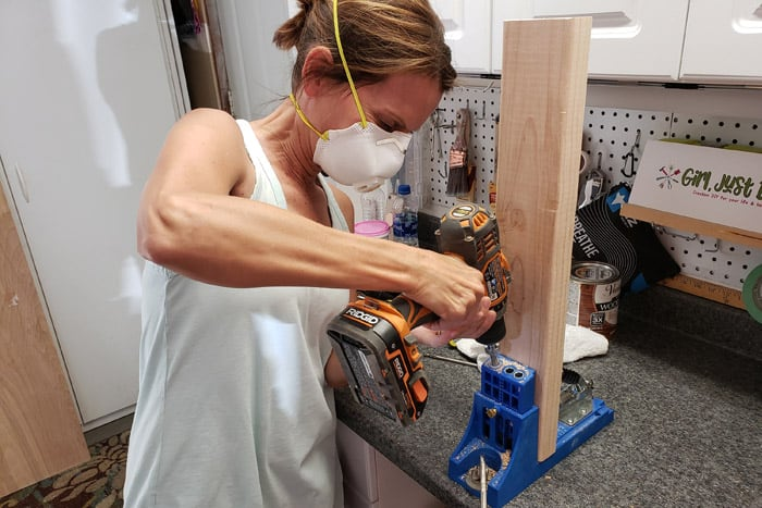 Woman drilling pocket holes into 2x4s with cordless drill