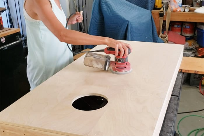 Sanding top of cornhole board with orbital sander.