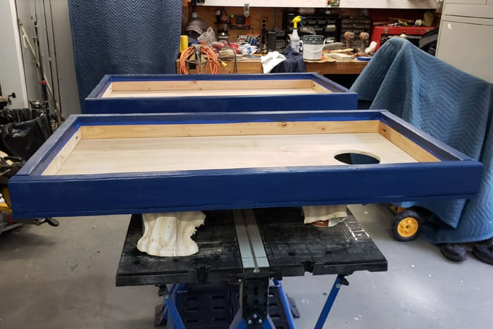 Both cornhole boards painted blue drying on workbench