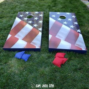 Set of cornhole boards on grass with beanbags.