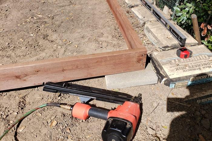 Framing nail gun laying near 2x6 frame.