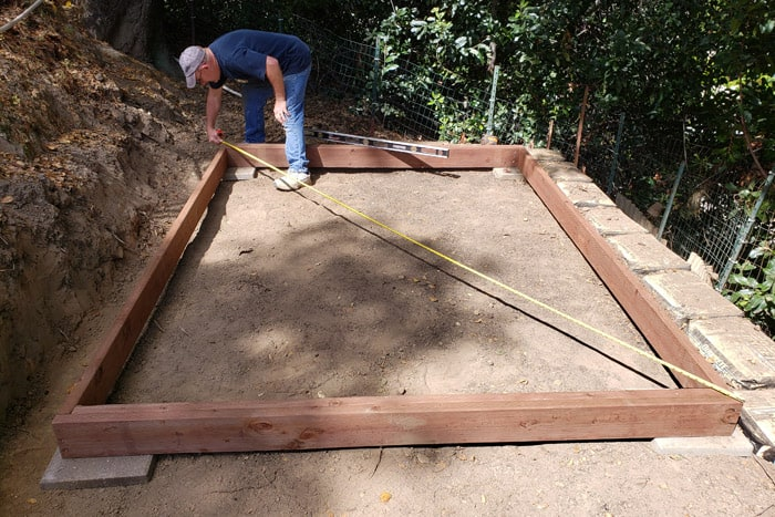 Man measuring across wood frame corner to corner.