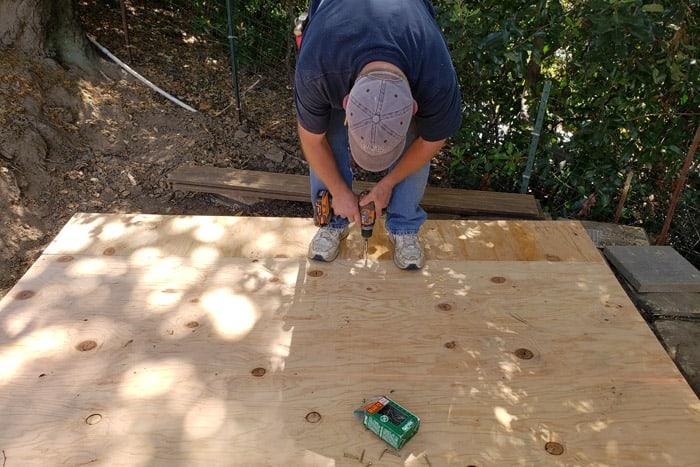 Man screwing plywood onto wood frame