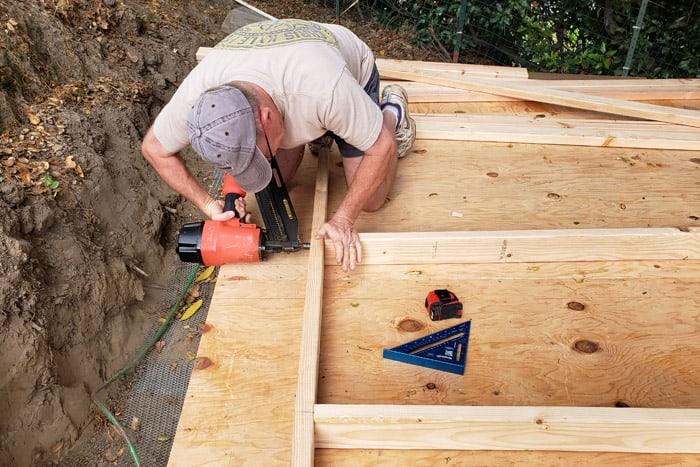 Man nailing into wall framing