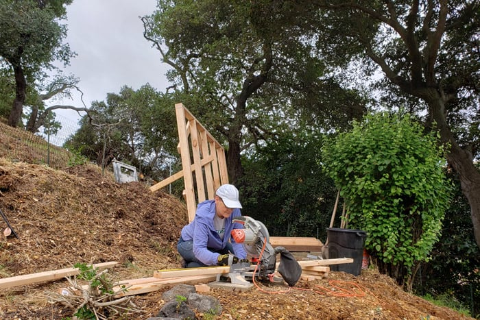 Woman crouched at saw on hillside path cutting wood.