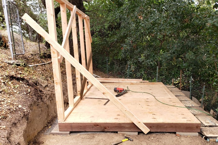 Side shed wall installed and braced on platform.
