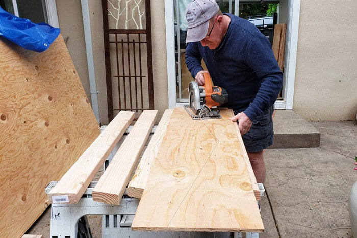 Man cutting plywood into truss gusset.